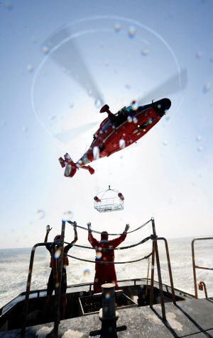 Deadly Duty: Arron Arking and Capt. John Bodin, both commercial tow-boat operators, release a rescue basket lowered from an MH-65 Dolphin helicopter crew from Coast Guard Air Station Atlantic City, N.J., during training off the coast of Atlantic City Friday, Aug. 2, 2013. Helicopter crews train with the rescue basket to ensure proficiency during an actual emergency. U.S. Coast Guard photo by Petty Officer 3rd Class Cynthia Oldham - Petty Officer 3rd Class Cynthia Oldham