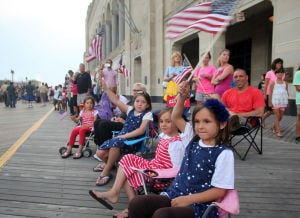 AC Salutes Armed Forces Parade: From right, Addison Burgess, her sisters Ashlyn and Angie, wave flags with their family, all from Egg Harbor Township, the Atlantic City Salute Armed Forces parade on the Atlantic City Boardwalk, Monday June 24, 2013  - Photo by Vernon Ogrodnek