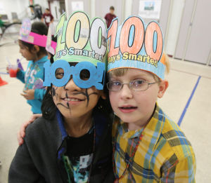 IN THE SCHOOLS CARNIVAL 100: Third grade students Supiya Modsuwan (left) and Landon Taylor, wear 100 days hats they created. The Glenwood Avenue Elementary School in Wildwood, celebrated the 100th Day of School with sports-themed activities held in the school's all-purpose room. Tuesday Feb. 11, 2014. (Dale Gerhard/Press of Atlantic City) - Dale Gerhard