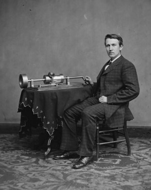 Thomas Edison sits with a phonograph, one of his inventions.