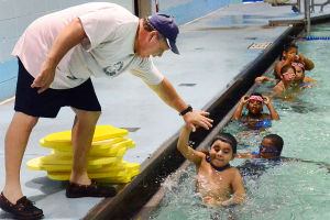 SWIM CLASSES: Instructor Dave Demarest of Galloway high-fives John Rojhon, 8, of Atlantic City while conducting the lessons poolside. Monday July 15 2013 Swimming lessons at the pool of the Martin Luther King School Complex in Atlantic City. (The Press of Atlantic City / Ben Fogletto) - Ben Fogletto