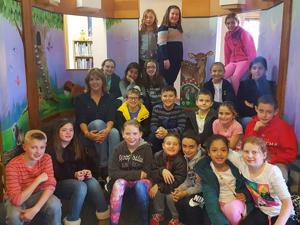 """<p>A Center School class visited the Thomaston Public Library Monday, November 28, where students picked out books to help """"expand their minds,"""" said Library Assistant Melissa Goldrick. TCS students stand with local artist Sherrie Fitzpatrick, who recently completed the mural in the stage area of the Children's Department. The mural depicts an Irish countryside theme, with woodland creatures and hillside scenes. (Times Photo, Piazzaroli)</p>"""
