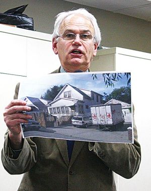 <p>Juniper Park Civic Association President Bob Holden holds a picture of a commercial truck sitting in the driveway of a residential home, a violation of city parking laws.</p>
