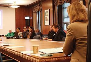 <p>Borough President Melinda Katz, right, listens as Dr. Jessica Kattan, fourth from left, gives a presentation to the Queens Borough Board on Ebola preparedness and the science of the deadly disease on Monday at Borough Hall.</p>
