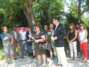 <p>Judy Limpert, president of the Bayside Business Association, center, said the pink clothing bin, left rear, placed near the historic Lawrence Cemetery is a sacrilege. With her are Assemblyman Ed Braunstein and civic leaders.</p>