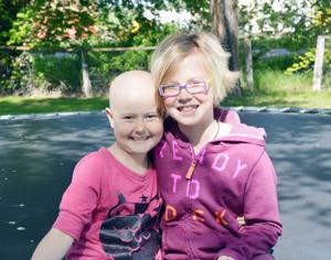 """<p>Meg, left, and Sirri Jensen are shown last week sitting on the trampoline at their home. At left is the logo, """"Megatronstrong,"""" that signifies Meg's current fight against cancer.</p>"""