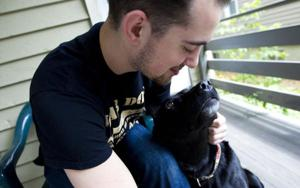 <p><strong>Katie Klann / Milwaukee Journal Sentinel<!--p:Photo credit--></strong></p><p>Cody Crangle, 23, plays with his retired Marine service dog, Flo, 8, on his porch in Milwaukee. Crangle adopted Flo after both served in Afhanistan. One day in a park, Flo started limping, and a veterinarian said Flo had torn her ACL.<!--p:Photo text--></p>