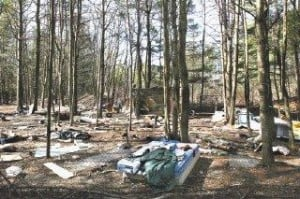 DEBRIS FIELD — The remains of the former shelter in Tent City can be seen in the middle of the photo, while the property itself is littered with trash.