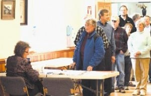 <p>Cindy Westover, supervisor of the checklist, handles a long line of Walpole voters Tuesday afternoon.</p>