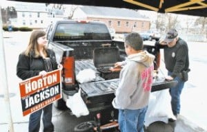 <p>Winchester school board candidate Richard Horton grills hot dogs on the back of his pickup truck in the Winchester Town Hall parking lot Tuesday as fellow school board candidate Elisha Jackson looks on and Winchester Animal Control Officer Gene Park waits for the dogs to be ready.</p>
