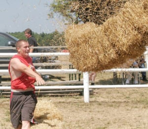 <p>A square bale of hay comes apart after being heaved by Jason Kaminski during the hay bale and roll competition Thursday afternoon at the cow show pen at the Mason County Fairgrounds during the Western Michigan Fair.</p>
