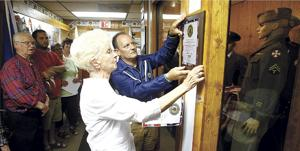 <p>Pat Lange helps Florence Hamilton place a plaque at the Hamilton Room inside the Ludington American Legion Tuesday. The room holds uniforms worn by Florence Hamilton's husband, Dick, and grandson Mark along with uniforms donated by other local families.</p>