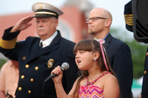 <p>Brynn Fortner, 8, of Ludington sings the National Anthem at the Blessing of the Badges during Friday Night Live.</p>
