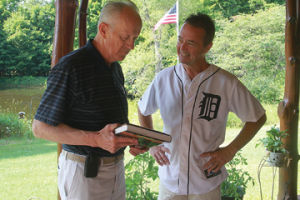 <p>Dr. Bill Anderson presents Scott Dumas with a copy of his new book. Dumas continues his recovery after being involved in a hit and run accident in the  Shop-N-Save parking lot in the spring.</p>