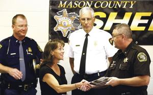 <p>Mason County Sheriff Kim Cole shakes Mason-Oceana 911 dispatch supervisor Pat Dancz's hand in giving her a Lifesaving award.</p>