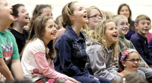 <p>Students react to Michigan Chillers author Johnathan Rand as he shares a funny story with students at Foster Elementary School Wednesday. Rand has written many books about his home state including