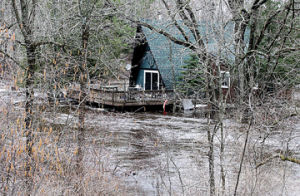 <p>A home along the south branch of the Pere Marquette River near Anthoney Road is flooded Monday as the river has risen near the flood stages following five plus inches of rain the past couple of days.</p><p></p>