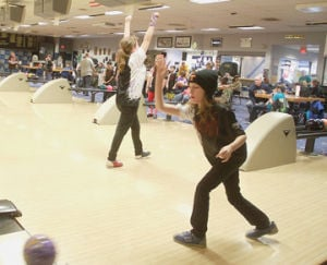 <p>Abby Dulin cheers after her turn at bowling league Saturday morning at Country Lanes Bowling Center as Amelia Larson releases her ball down the lane. The leagues is for kids up to high school age.</p>