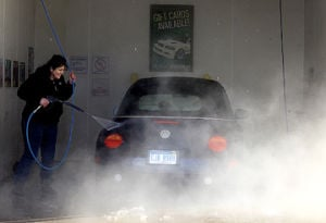 <p>Andrea Tomes of Ludington washes her Volkswagen Beetle Wednesday. The sunshine drew many out to clean their vehicles.</p>