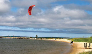<p>A kite boarder holds onto his kite as he walks the inner harbor beach Wednesday. High winds have made for great sailing on Lake Michigan this week.</p>