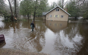 <p>Gary DeVos pus on a pair of wadders to walk to the back door of his house Monday. His home on the south branch of the Pere Marquette River is flooded.</p>