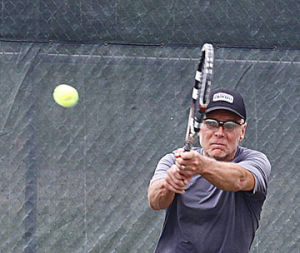 <p>Vic Burwell returns a shot during Saturday's Ludington Tennis Tourney. Sunday will be the doubles portion of the tourney.</p>