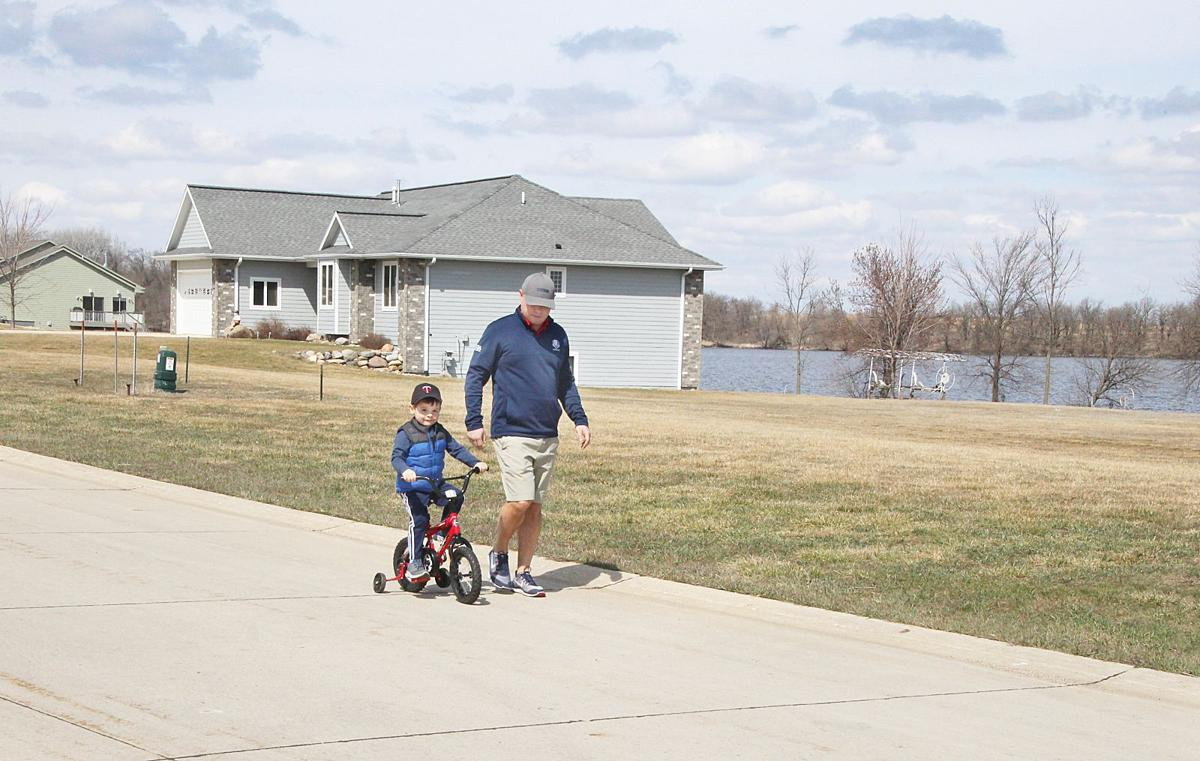 Jared Rahe walks with his son Maddox, 3, on a sunny day in March, along West Bay Road, in West Bay Estates, on the shore of Silver Lake, in Lake Park, Iowa. Silver Lake can be seen in the distance. The Dickinson County community has benefited in recent years from housing assistance programs. (Photo: Russ Oechslin, Sioux City Journal)