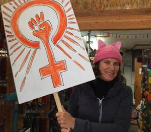 <p>Lisa Thorpe, a local artist displays the protest sign she made at a sign-making event. Leah Gold and Jennifer Utsch hosted the event in Healdsburg.</p>