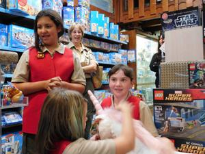 "<p>Troop leader Danelle Jacobs and the members of the Unicorns receive their mascot ""Scout"" from Toy Works in support of their petition to the national council of Boy Scouts to join the organization.</p>"