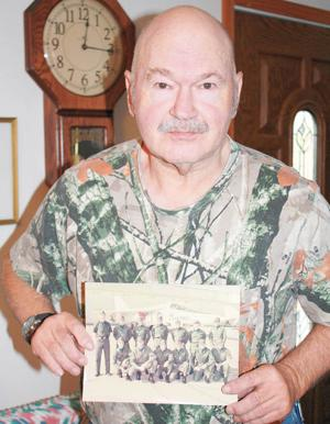 <p>Air Force veteran Larry Bittner holds a photo of his unit during his time in the service. He is second from the right, front row.</p>