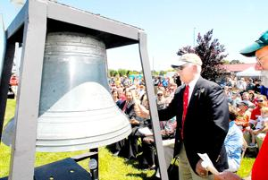 <p>Former President of the Chesapeake Bay Maritime Museum John R. Valliant bangs a hammer on a 1910 Fog Bell from a Chesapeake Bay lighthouse Saturday during the museum's 50th anniversary celebration.</p>