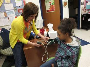 <p>McClure Elementary nurse Christy Johnson takes second-grader Naomee Mayfield's blood pressure Friday morning in the school clinic. Johnson recently was named Region 10 School Nurse of the Year.</p>