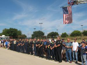 <p>Members of the Flower Mound police and fire departments observed a moment of silence Friday morning in honor of Harris County Sheriff Deputy Darren Goforth, who was shot and killed Aug. 28. About 50 residents also attended the event, which took place in front of The Flower Mound. </p>