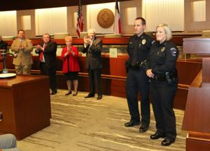 """<p><span style=""""font-size: 12px;"""">Mesquite police officers Ryan Nielson and Autumn Soto, right, receive a standing ovation during Monday's council meeting. The officers were recognized by the police department for saving Hector Valles from a burning vehicle the early morning of April 19.</span></p>"""