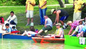 <p>Participants prepare to sail their cardboard creations during last year's Rowlett Cardboard Boat Regatta.</p>