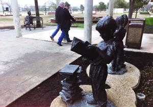 <p>Visitors to the Rowlett Public Library walk between two displays of public art, the Mark Twain statue, left, and the Bookworms, right.</p>