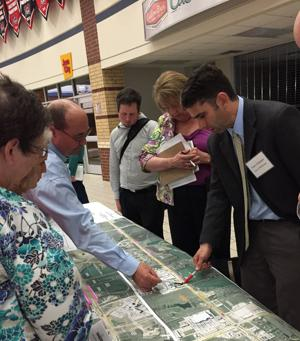<p>McKinney Traffic Manager Gary Graham, right, talks with residents about proposed traffic signals and other access points along U.S. Highway 380 during a public meeting in April.</p>