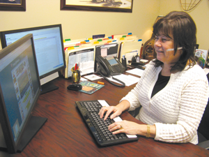 Cheri Church, of Travel Brokers, Inc. in Fenton, constantly checks her computer for the latest travel information, including airline fees that will affect her clients.