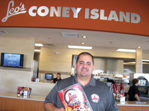 Leo's Coney Island owner Ken Vlahadamis holds up a menu featuring Greek specialties, American favorites and all-day breakfast.