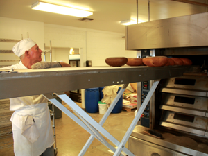 Steven Wells removes baked bread from the oven at Crust bakery in Fenton. Windows allow passers by to see fresh baked good being made daily.