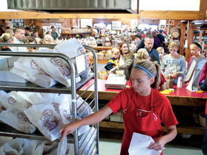 Kassidy Scheffer, 15, of Hartland, bags doughnuts at Spicer Orchards in Hartland Township last weekend, the official start to the fall cider mill season.