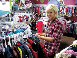 Store manager Bobbi Anne Green shows the racks of baby and children's clothes, neatly organized by gender, size and style at Spoiled Rotten.