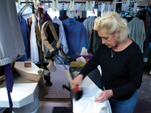 """Diana Kelp irons the collars of dress shirts with one swipe. """"I have trouble slowing down,"""" she said. About 100 shirts will be pressed per day."""