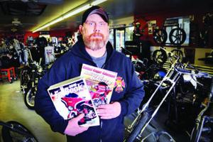 <p>Jason Mook, technical editor for Maverick Publishing, shows Drag Specialties' 2016 FatBook and the March 2016 edition of American Bagger magazine. Mook rebuilt the 2014 FLHX Street Glide that graces the cover of both magazines.</p>