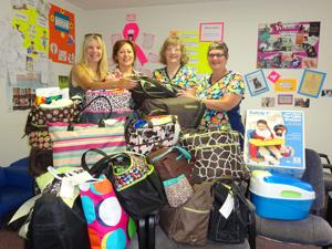 WIC accepts diaper bag donation from Community Women's Club