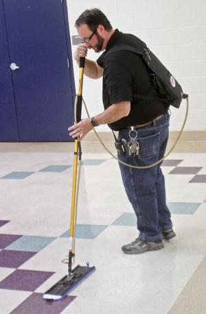 Tony Carnes uses the new green cleaning floor waxing system at Carpenters Middle School