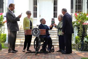 <p>Gov. Greg Abbott, center, presents the Texas Legislative Medal of Honor to Nell Denman in honor of her late brother, World War II hero Edwin Dyess, during a ceremony Wednesday in Austin. Watching, from left, are author John Lukacs, Bettye Denman and Judge Ed Denman.</p>
