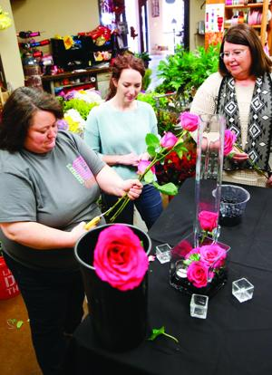 <p><strong>Chapman's Florist designer Stacy Jones, left, clips roses while Children's Advocacy Executive Director Rebecca Peevy, center, and services coordinator Kitty Coursey, right, decide on the table decorations for the Sweetheart Soiree event Saturday at Love Civic Center.</strong></p>