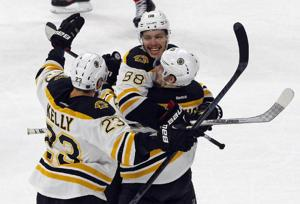 <p>Boston Bruin David Pastrnak, center, basks in his game-winning overtime goal against the Carolina Hurricanes Sunday with teammates Torey Krug, right, and Chris Kelly in Raleigh, N.C.</p>