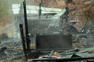 <p>Charred wood smolders around a hog feeder after the April 7 fire that destroyed a shed and garage at the Rogers' residence in Hebron Township. Four hogs died in the blaze and some equipment and tools were lost.</p><div> </div>